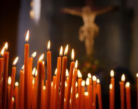 Accendere una candela online: candelabro pieno di candele con in sfondo Gesù